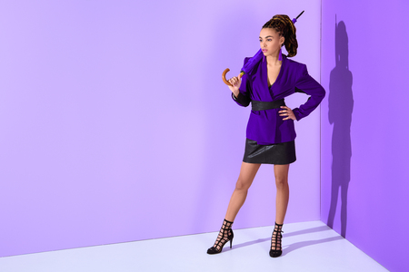 Fashionable mulatto girl posing in purple jacket with umbrella at ultra violet wall background Stock Photo