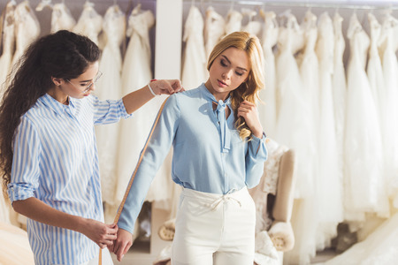 Young woman and professional tailor taking measurements in wedding fashion shop Stock fotó