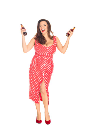 Happy plus size woman with bottles of soda looking at camera isolated on white background