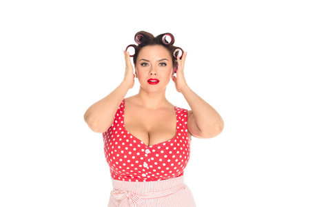 Attractive plus size woman with curlers in hair looking at camera isolated on white background