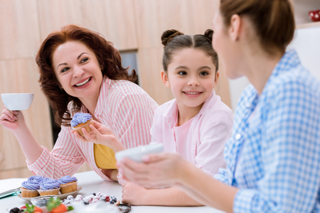 Three generations of women spending time together on kitchen and eating desserts with tea at kitchen