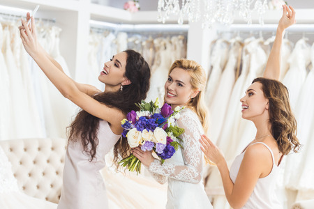 Young smiling bride with bouquet and bridesmaids taking selfie in wedding fashion shop