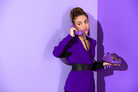Fashionable mulatto girl talking on rotary phone at ultra violet wall background