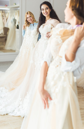 Young brides holding dresses in wedding atelier