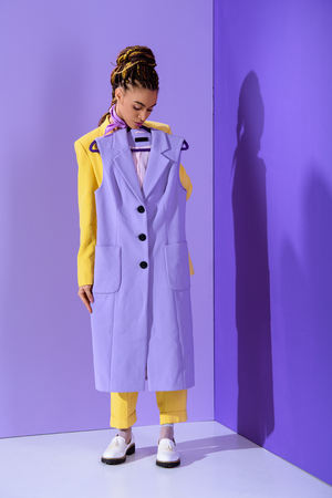 Elegant African American girl in yellow suit holding purple waistcoat, on trendy ultra violet background