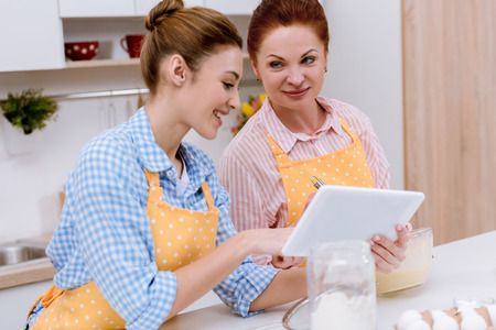 Young woman and her mother using tablet together at kitchen while cooking Stock Photo