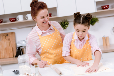 Happy grandmother with little granddaughter rolling dough for cookies Stock Photo