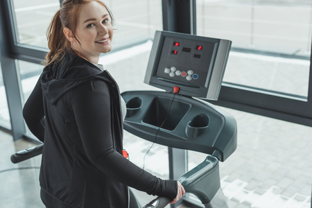 Curvy girl smiling while on treadmill in gym