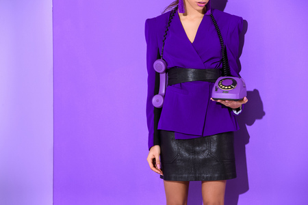 Cropped view of elegant girl posing in purple jacket and holding vintage rotary phone at ultra violet wall background