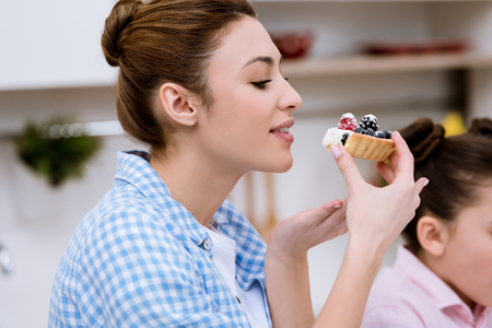 Attractive young woman eating delicious tart with berries 스톡 콘텐츠