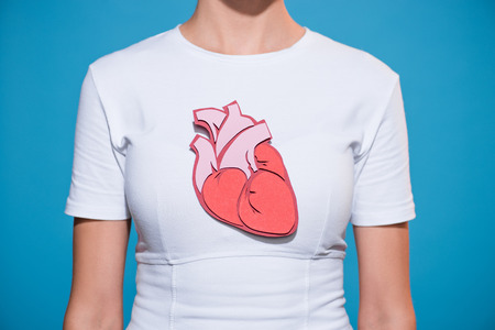 Cropped shot of woman in white tshirt with paper made heart on blue backdrop 免版税图像