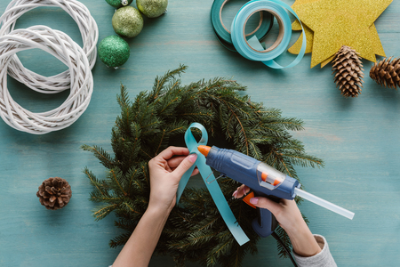 Cropped shot of woman decorating handmade Christmas wreath with blue ribbon on blue wooden surface