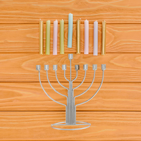 Top view of traditional Jewish menorah and colorful candles on wooden tabletop, hannukah holiday concept
