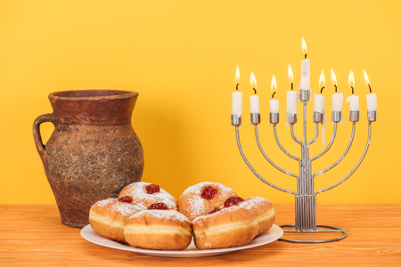 Close up view of sweet doughnuts, clay jug and menorah on wooden surface on yellow backdrop, hannukah concept Stock Photo