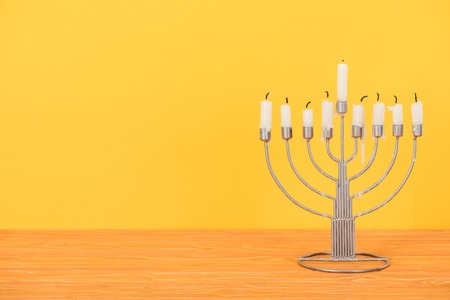 Close up view of menorah with candles for hannukah holiday celebration on wooden tabletop isolated on yellow, hannukah concept