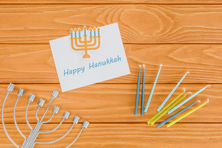 Flat lay with happy hannukah card, candles and menorah on wooden surface, hannukah concept