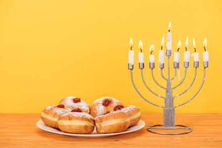 Close up view of sweet doughnuts and menorah with candles on wooden surface isolated on yellow, hannukah concept Stock Photo