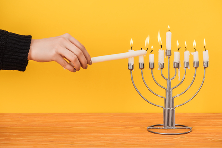 Partial view of woman lighting candles on menorah isolated on yellow, hannukah holiday concept Stock Photo