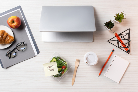 Top view of container with vegetable salad and sticky note with inscription lunch time, laptop and office supplies on table