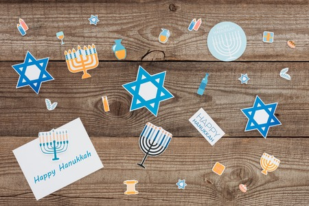 Flat lay with happy hannukah card and holiday paper signs on wooden tabletop, hannukah concept Stock Photo