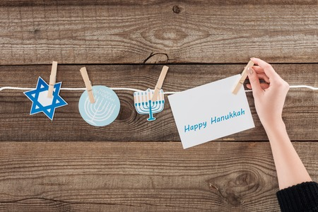 Cropped shot of woman pegging happy hannukah card on rope with holiday paper signs on wooden surface, hannukah concept