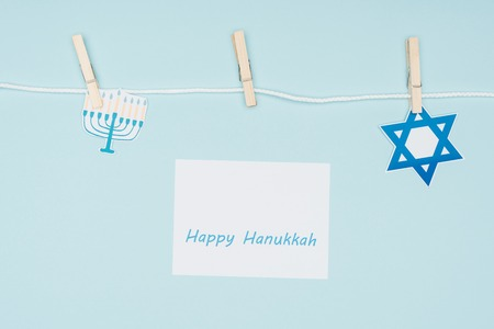 Top view of happy hannukah card and holiday paper signs pegged on rope isolated on blue background, hannukah concept Stock Photo