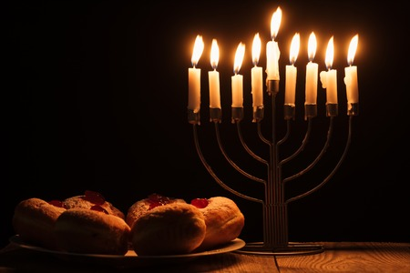 Close up view of traditional sweet doughnuts and menorah with candles on black background, hannukah holiday concept