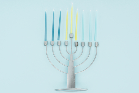 top view of menorah and candles on blue background, hannukah celebration concept