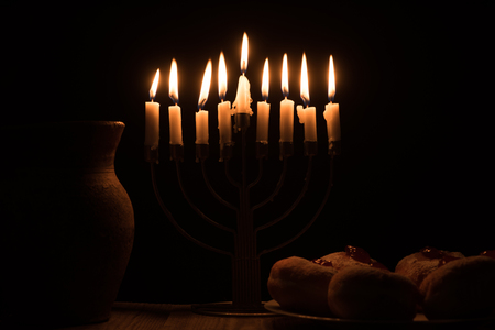 close up view of traditional sweet doughnuts, clay jug and menorah with candles on black background, hannukah holiday concept