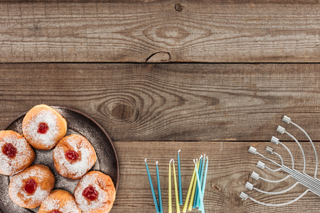 Top view of sweet donuts and menorah with candles on wooden tabletop, hannukah celebration concept