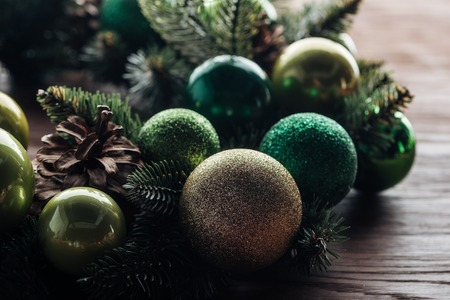 Close up view of pine tree wreath with green Christmas balls on wooden background