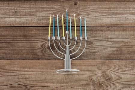 top view of traditional jewish menorah with blue and yellow candles on wooden tabletop, hannukah holiday concept Stock Photo