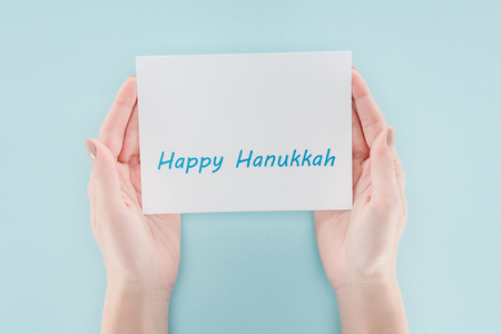 Cropped shot of woman holding card with happy hannukah lettering on blue background, hannukah concept Stock Photo