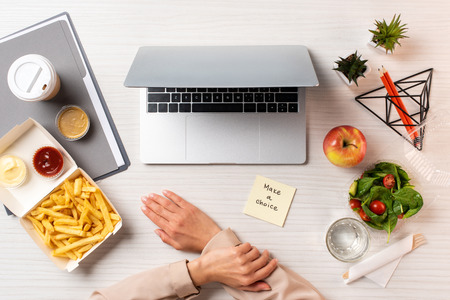 cropped shot of businesswoman, laptop, note with inscription make a choice and healthy food with junk food at workplace