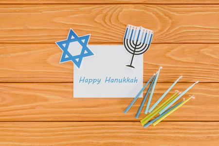 flat lay with happy hannukah card, candles and paper holiday signs on wooden tabletop, hannukah concept Stock Photo