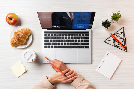 cropped shot of female hands, laptop with booking website and lunch on table in office 版權商用圖片