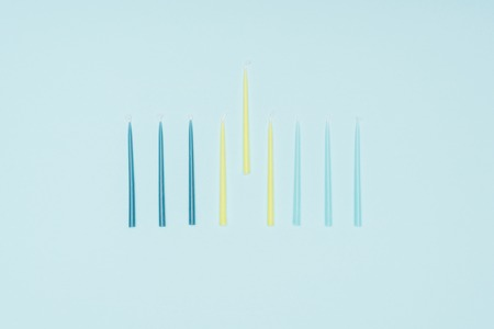 Flat lay with blue and yellow candles for hannukah holiday isolated on blue background, hannukah concept