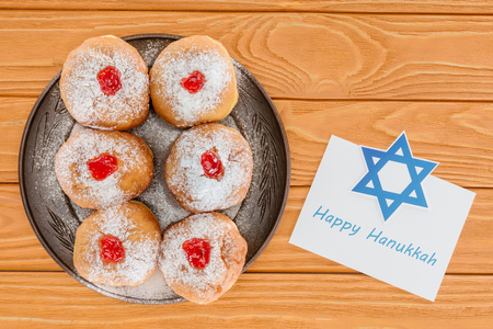 Top view of sweet donuts and happy hannukah card on wooden tabletop, hannukah celebration concept Stock Photo