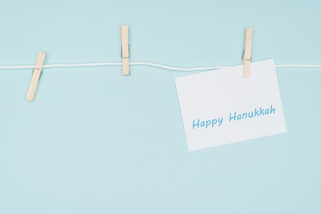 top view of happy hannukah card pegged on rope with clothes peg isolated on blue, hannukah concept