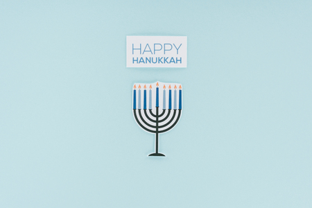 Top view of happy hannukah card and paper menirah sign isolated on blue background, hannukah concept