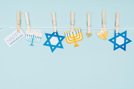 Vue de dessus des panneaux de papier de vacances de Hannukah chevillés sur une corde isolée sur fond bleu, concept de Hannukah