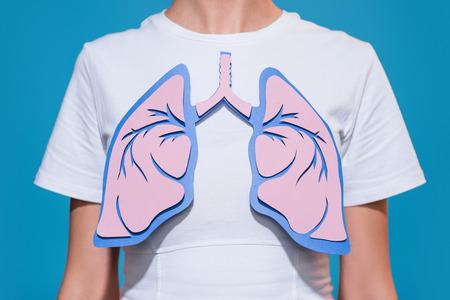 Teilansicht einer Frau im weißen T-Shirt mit aus Papier gefertigten Lungen auf blauem Hintergrund
