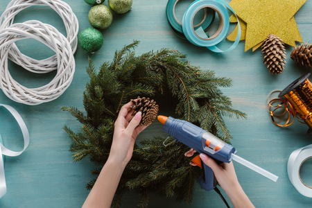 cropped shot of woman decorating handmade christmas wreath with pine cone on blue wooden surface Imagens