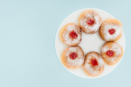 top view of traditional sweet doughnuts for hannukah holiday isolated on blue, hannukah concept Stock Photo