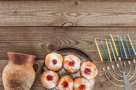 top view of sweet donuts, clay jug and menorah with candles on wooden tabletop, hannukah celebration concept