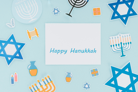Flat lay with hannukah holiday paper signs and happy hannukah card isolated on blue background, hannukah concept