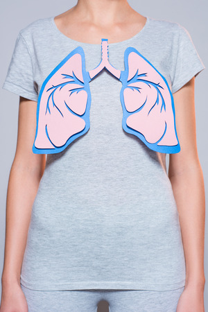 partial view of woman with paper made human lungs on grey background