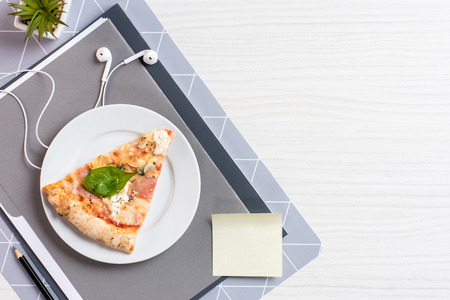 top view of pizza on plate, blank note and earphones on white wooden table Banque d'images - 112122349