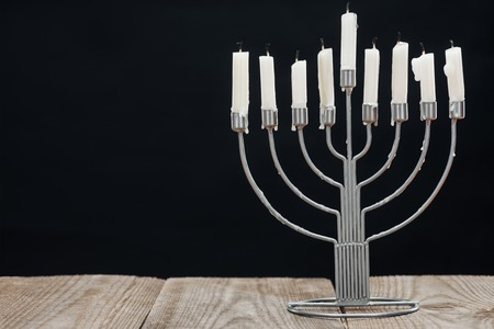 Close up view of Jewish menorah with candles for hannukah holiday celebration on wooden tabletop isolated on black background, hannukah concept Stock Photo