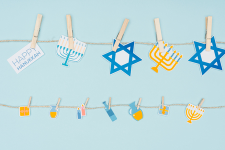 Top view of hannukah holiday paper signs pegged on rope isolated on blue background, hannukah concept